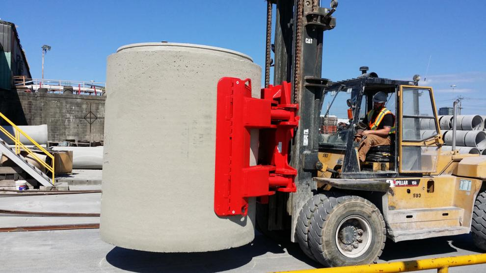 Massive concrete pipe clamp mounted on large forklift